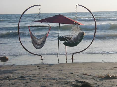 Two C-Frames with hanging Beach Swings, and a standing B-B-Q in the surf.